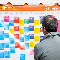 A man looks over the Boston Book Festival schedule posted in Copley Square in Boston's Back Bay.