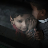 A Palestinian schoolboy whispers to his classmate inside a classroom at UNRWA's (UN Relief and Works Agency) primary school in Beit Lahia in the northern Gaza Strip on January 24, 2009. Some 200,000 Gaza children returned to school for the first time since Israel's offensive, many having lost family members, their home and their sense of security. The main UNRWA centre and several schools were destroyed by Israeli bombing during the 22-day war.