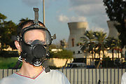 Israel, Haifa bay, A man wearing a gas mask at a protest against air pollution. The oil refinery in the back ground