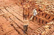 Workers load finished bricks for transport out of the kiln on April 14, 2016 in Dhading district, Nepal. Despite a national law that bans children under the age of 14 from working, many work alongside their families in the country's brick making industry. Ann Hermes/© The Christian Science Monitor 2016