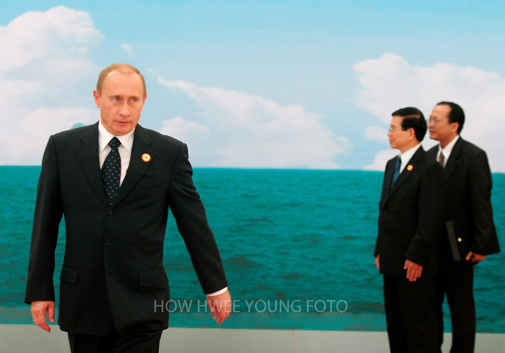 epa00866085 Russia's President Vladimir Putin walks away after bidding farewell to Vietnam's President Nguyen Minh Triet (2nd L) at the end of the Asia-Pacific Economic Cooperation (APEC) Summit in the National Convention Centre in Hanoi, Vietnam on Sunday 19 November 2006.  EPA/HOW HWEE YOUNG