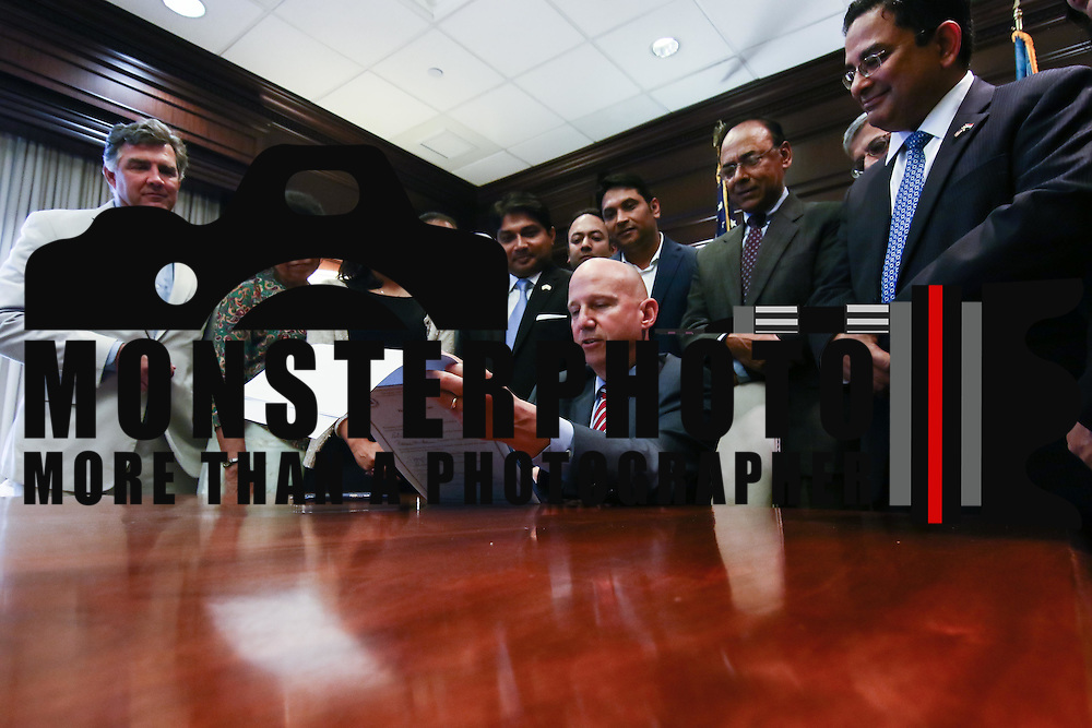 Gov. Markell (CENTER) looks over the bill before signing into law the creation of a Commission on Indian Heritage and Culture while members of Delaware's Indian committee watch Thursday, Sept. 01, 2016, at the Carvel State Office Building in Wilmington.