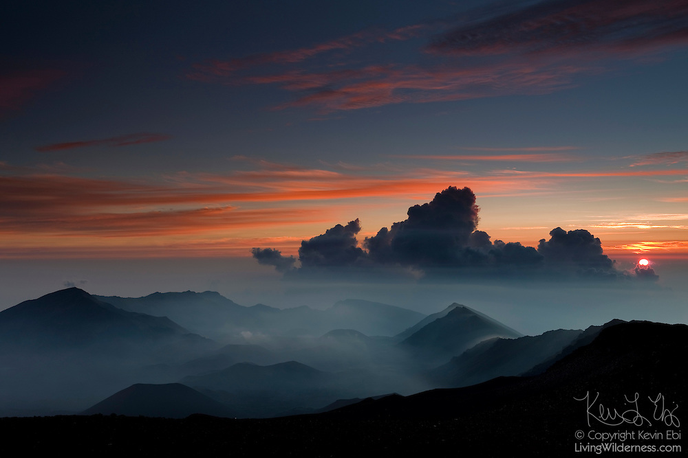 The sun rises behind storm clouds developing over the crater in Haleakala National Park, Maui, Hawaii.