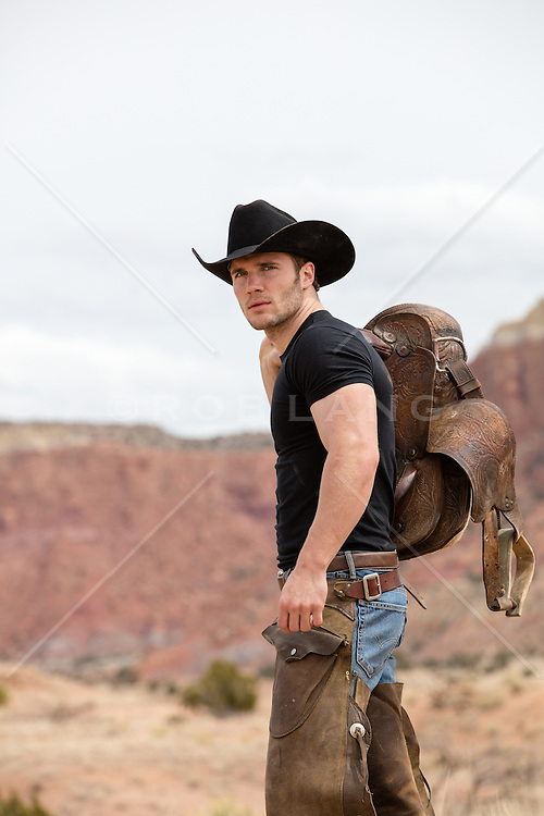 hot cowboy holding a saddle outdoors in the mountains