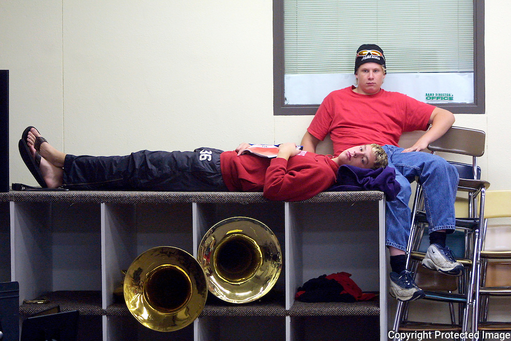 "Senior tuba players  Brandon Punt, left, and Darren Hogland, relax in the band room before leaving for Marshall, Minnesota, for the first field competiton of the year for MOC-Floyd Valley's High School's band.  ""The tuba section is the low stress section of the band,"" said Punt, who was assigned the instrument in the 5th grade.  The MOC-Floyd Valley High School band has won numerous state and national awards for their excellence and is made up 180 of the school's 360 students.  The band members develop a strong bond during the year."