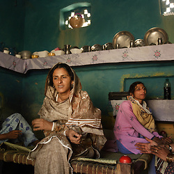 Left to right, Ikbal Mai, Mukhtar Mai, and Shanza Sehr sit together inside Mukhtar Mai's home, Meerwala, Pakistan, April 27, 2005. Mai, 33, went against the Pakistani tradition of committing suicide when she brought charges against the men who gang raped her nearly three years ago. With money from the ruling she opened two schools, one for girls, the other for boys. Mai cited that education is the only thing that will stop such acts from happening. Ikbal Mai, is the mother of Shanza Sehr, who is a teacher at the girls school.