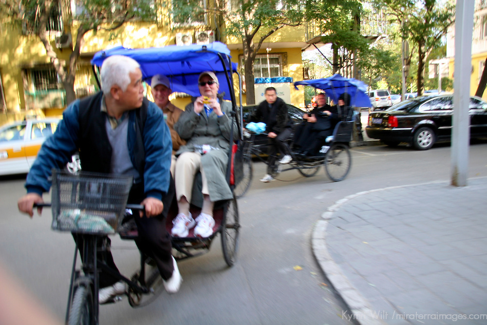 Asia, China, Beijing.  Rickshaw pedicabs turn the corner taking tourists into the hutong neighborhoods of Beijing.
