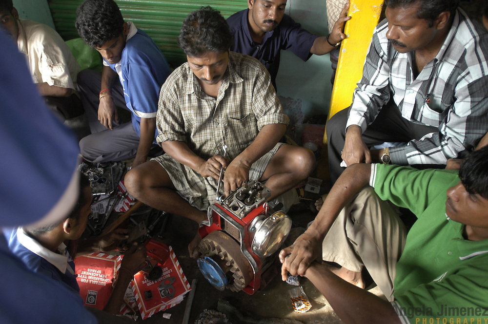 Mechanic Karthik, center, helps fishermen repair their engines at an emergency repair center operated by the South Indian Federation of Fishermen Societies (SIFFS), an Indian NGO, in Arukattuthurai, a fishing village in Tamil Nadu, India on January 27, 2005, after the area was struck by the Indian Ocean Tsunami on December 26, 2004. Generated by an earthquake on the ocean floor, the tsunami devastated the fishing industry along the southeastern coast of India.