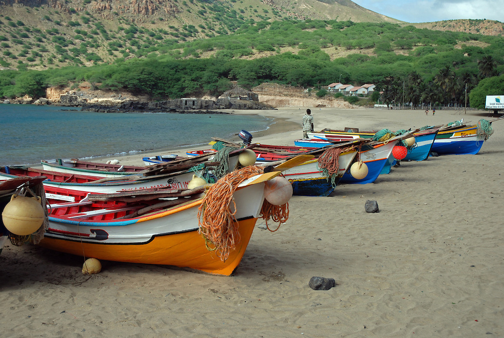 Fishing boats hauled up on the beach. Tarrafal, North west Santiago, Cape Verde Islands (Cabo Verde).  Artisanal fisheries are still very important in the Cape Verdes. Many of these small boats are simply rowed by oars, some have small outboard motors.  Tarrafal, or Villa de Tarrafal,  is a small fishing port on the north western tip of Santiago.  It has a beautiful sandy beach.  Typical species caught include yellowfin tuna (Thunnus albacares), big-eye tuna (Thunnus obesus) and African hind (aka bluespotted seabass)(Cephalopholis taeniops).