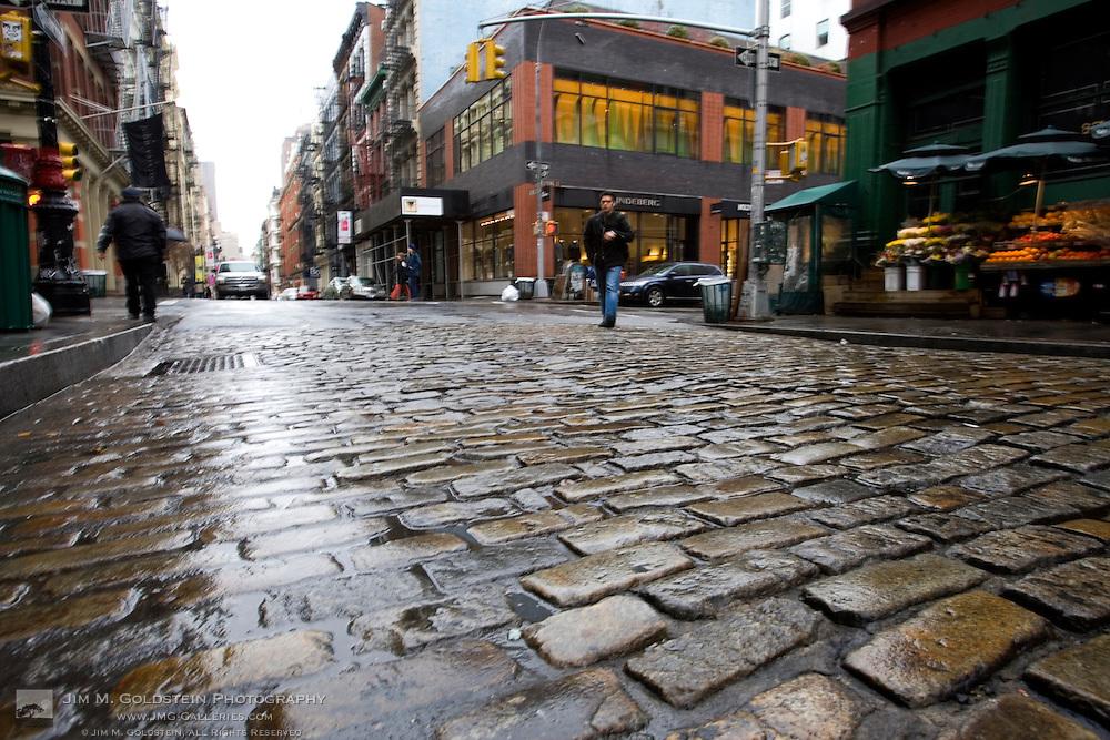 A pedestrian crosses Greene Street in New York City's SoHo district in the rain