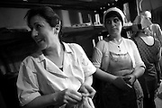 """Some baker chat during a rest at night in their bakery. This image is part of the photoproject """"The Twentieth Spring"""", a portrait of caucasian town Shushi 20 years after its so called """"Liberation"""" by armenian fighters. In its more than two centuries old history Shushi was ruled by different powers like armeniens, persians, russian or aseris. In 1991 a fierce battle for Karabakhs independence from Azerbaijan began. During the breakdown of Sowjet Union armenians didn´t want to stay within the Republic of Azerbaijan anymore. 1992 armenians manage to takeover """"ancient armenian Shushi"""" and pushed out remained aseris forces which had operate a rocket base there. Since then Shushi became an """"armenian town"""" again. Today, 20 yeras after statement of Karabakhs independence Shushi tries to find it´s opportunities for it´s future. The less populated town is still affected by devastation and ruins by it´s violent history. Life is mostly a daily struggle for the inhabitants to get expenses covered, caused by a lack of jobs and almost no perspective for a sustainable economic development. Shushi depends on donations by diaspora armenians. On the other hand those donations have made it possible to rebuild a cultural centre, recover new asphalt roads and other infrastructure. 20 years after Shushis fall into armenian hands Babies get born and people won´t never be under aseris rule again. The bloody early 1990´s civil war has moved into the trenches of the frontline 20 kilometer away from Shushi where it stuck since 1994. The karabakh conflict is still not solved and could turn to an open war every day. Nonetheless life goes on on the south caucasian rocky tip above mountainious region of Karabakh where Shushi enthrones ever since centuries."""