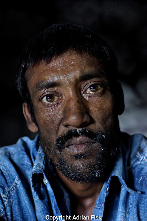 The tired face of the plastic waste carrier stares into the camera. Like most labourers in the slum he gets paid Rs80 ($1.80) for a 12 - 14 hour day, many labourers do not even have their own home in the slum but share a floor with other workers.