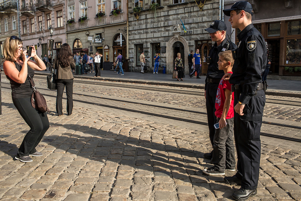 LVIV, UKRAINE - SEPTEMBER 15, 2015: Vasil Spodayk, 33, and Roman Katalakh, 22, right, both members of the new police, pose for a picture with tourists in Market Square, the tourist-friendly central square in Lviv, Ukraine. In an effort to reform the notoriously corrupt Ukrainian police force, an entirely new force has been established in several cities, including Kiev and Lviv, with a primary focus on patrolling the streets. CREDIT: Brendan Hoffman for The New York Times