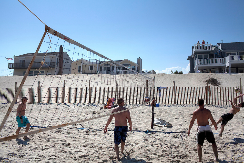 Long Beach Island, NJ - June 29, 2013 :  Houses are missing in the background as friends play beach volleyball at Beach Haven on Long Beach Island, NJ on June 29, 2013. People are returning to the beaches for the summer after recovery efforts post Hurricane Sandy.