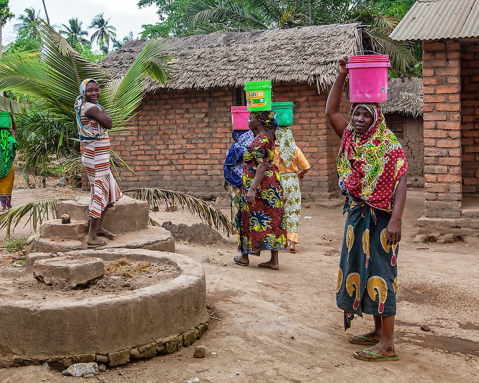 Women carry water from their village pump to their homes each morning. Clean water is supplied by simple pumps drilled deep into the ground by MSABI, a local NGO providing clean water and sanitation services.