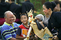 Thai family enjoying a puppet show.