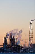 As the sun set behind, an oil refinery emits smoke and steam into the cold winter air.