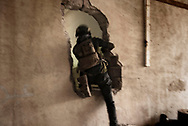 Iraq, Mosul: As they advance house by house members of the Golden Division pass through holes in the wall made by ISIS fighters to avoid to be seen by Iraqi army forces. Alessio Romenzi