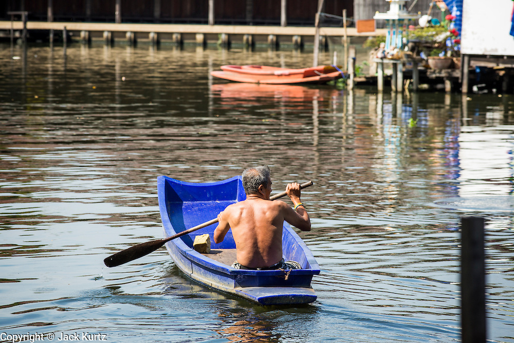 03 JANUARY 2013 - BANGKOK, THAILAND: A man paddles his canoe through Phra Khanong canal near Wat Mahabut. Just a few minutes from downtown Bangkok, the neighborhoods around Wat Mahabut interlaced with canals, still resemble the Bangkok of 60 years ago. Wat Mahabut is a large temple off Sukhumvit Soi 77. The temple is the site of many shrines to Thai ghosts. Many fortune tellers also work on the temple's grounds.   PHOTO BY JACK KURTZ