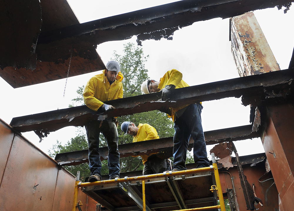 """In this Sept. 20, 2011 photo, Marco Federico, left, Adam Jenkins, center, and David Facenda, right, disassemble one of Connecticut College's steel houses on campus in New London, Conn. Steel panels from the house will be shipped to Philadelphia and rehabilitated there, until it's ready to be shipped back and reassembled to look as it did when it was sold in 1933 as the """"house of tomorrow.""""  (AP Photo/Jessica Hill)"""