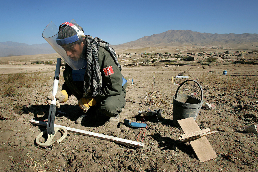 A member of a Halo Trust team searches for mines on the outskirts of a village. Afghanistan remains one of the most heavily mined countries in the world. A mine clearance team from the Halo Trust have been working for more than a year in the small village of Kohe Safi and have removed 800 mines and 118 unexploded bombs. Kohe Safi, Afghanistan on the 1st of November 2007..Throughout the country the Halo Trust alone is working to clear 90 million square meters of mine fields containing some 640,000 mines, they estimate it will take them 18 years to complete this task..A break through in mine detection not seen since  World War II is due to speed things up in the coming year when Halo become the first civilian organisation to use H-STAMIDS (The Handheld Stand-Off Mine Detection System) a new combination tool with a metal detector and ground penetrating radar system. The H-STAMIDS remain classified and during recent trails in Afghanistan the device had to be returned to the US military at the end of each day. The new equipment should make mine clearance 2-3 times faster..