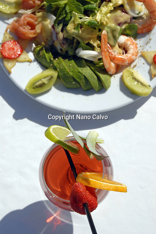Cocktail and a fresh salad in Tropicana, a popular beach restaurant in Cala Jondal, Ibiza