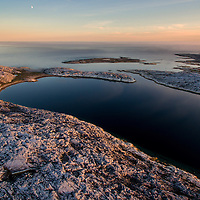 Canada, Nunavut Territory, Rankin Inlet, Moon sets above Marble Island on summer evening along western shore of Hudson Bay