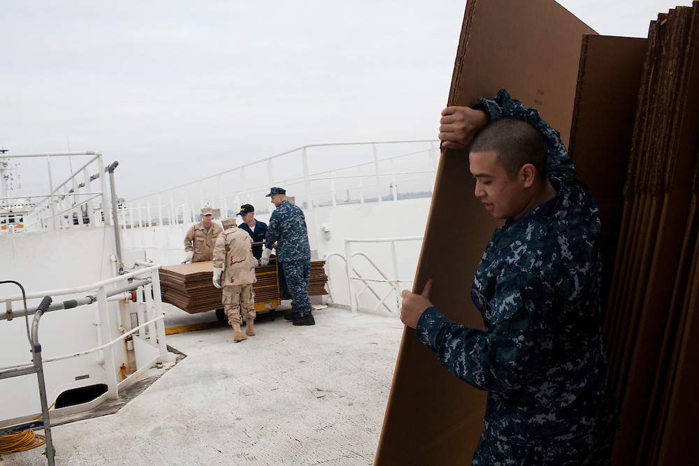 Sailors move cardboard boxes below deck on board the USNS Comfort, a naval hospital ship, before it gets under way to Haiti to assist earthquake victims on Saturday, January 16, 2010 in Baltimore, MD.