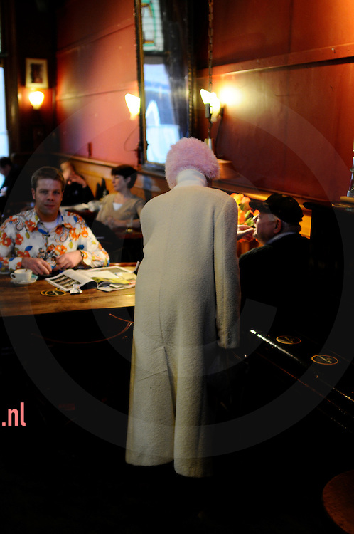 een vrouw met een vreemd hoofddeksel speekt een cafegast aan in het bolwerk (cafe) in enschede