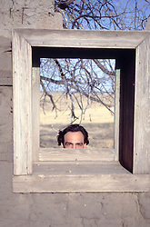 man peaking out from a wooden window