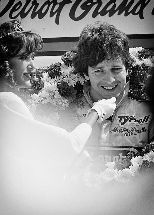 British Formula One rookie Martin Brundle celebrates his first podium at the 1984 Detroit Grand Prix. <br /> <br /> Fate and timing worked together to derail many careers during the decade. Martin Brundle and Arton Senna fought for the 1983 British F3 Championship, with Brundle finishing a very close second. They followed each other into F1 the next year, with Senna finishing second in Monaco. <br /> <br /> Three weeks later, Brundle captured  second place with an underpowered Tyrrell-Ford at the Detroit Grand Prix and seemed on top of the world...at least the equal of his old rival Ayrton Senna. <br /> <br /> Sadly, he broke both legs at the Dallas Grand Prix and had to abandon the rest of the season. Later, he learned that the FIA had disqualified both Tyrrells for rules violations and removed all their points for that season, including his second. <br /> <br /> Though he went on the win the Le Mans 24-Hour, and have a distinguished career for McLaren, and as a preeminent broadcast journalist for Formula One with SkyF1, he never again would experience the profound joy of that lost second place.
