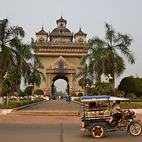 The Patuxai, Vientiane's answer to the Arc de Triomphe with a motorized tuk tuk in the foreground