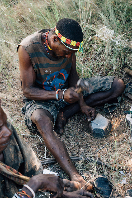 A male member of the Hadza tribe, (Mahia otherwise known as Yasaneda, which translates as 'lots of pot' because of his smoking habits), makes arrow heads out of old nails purchased at one of the surrounding markets. Yaeda Valley, Northern Tanzania. Photo by Greg Funnell, March 2016.