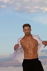 hot man taking off his shirt outdoors at sunset