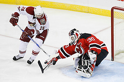 Mar 12, 2009; Newark, NJ, USA; New Jersey Devils goalie Martin Brodeur (30) makes a save on Phoenix Coyotes center Steve Reinprecht during the third period at the Prudential Center. The Devils defeated the Coyotes 5-2, and Brodeur moved to within one win of tying Patrick Roy for the all-time win record.