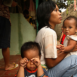 "Dian Dama Yanthi, 32, and her children, Galang, 3, and Gilang Rama, 1, are seen at their house in Tangerang, on the outskirts of Jakarta, Indonesia, April 19, 2006. Dian had an unsafe abortion and lost her best friend to an unsafe abortion. Both took the traditional medicine ""jamu."" Dian also had a massage from a traditional birthing attendant. Over two million abortions are performed in Indonesia every year, many by unskilled practitioners. Thousands of women survive but often with life-long disabilities. It is said by doctors and activists that a woman dies every hour in Indonesia due to unsafe abortions."