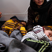 """Sadjad, 2, and his family are refugees from Kondos, Afghanistan. They are having a welcome rest in a warm temporary shelter near the train station, before they continue on to the Croatian border, on their way to Germany. After being threatened by the Taliban the family fled. Over the last month and a half they have walked through the snow-packed mountains of Afghanistan, taken a circuitous route through Pakistan (to avoid border control), and taken the harrowing boat ride from Turkey to Greece. Setaesh: """"Our babies were screaming and crying for food for days."""" It was really difficult-we threw our baggage away."""" Farashta, regarding the boat ride: """"I was really scared for my children."""" Presevo, Serbia, January 2016."""
