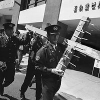 Police remove a huge wooden crucifix which a protestor had been carrying during anti-Iraq war and anti-American demonstrations infront of the American embassy, Tokyo, Japan. 2003