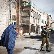 A Palestinian lady walks past a patrolling Israeli soldier. Image © Angelos Giotopoulos/Falcon Photo Agency