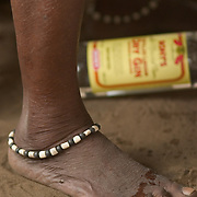 "Ankle bracelet and offering of gin at a ""coming out"" ceremony at a fetish shrine in Aflao, Volta Region, Eastern Ghana. A woman was released after spending three months in a small, dark room, hoping that she'd then be able to find a husband. Despite most Ghanaians being adamant followers of christianism or islam, many of them still maintain traditional beliefs. When facing a problem of any nature, some people will visit a local fetish shrine, looking for help. The main priest will consult the oracles and tell the person in need what has to be done for the problem to go away. People will typically be asked to ""serve"" the shrine for weeks, sometimes months, as their families pay the priest for their upkeep."