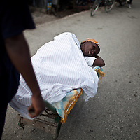 The number of cholera victims in Cité Soleil, a slum of Port-au-Prince, is increasing day by day exponentially, according to a doctor of Doctors Without Borders.///A woman carries a victim of cholera in a wheelbarrow to the nearest hospital  in the slum of Cite Soleil in Port-au-Prince.