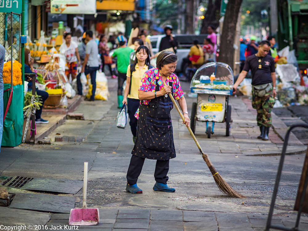 29 FEBRUARY 2016 - BANGKOK, THAILAND: A vendor sweeps up the sidewalk where she had been selling flowers in front of the Bangkok flower market early Monday. Many of the sidewalk vendors around Pak Khlong Talat, the Bangkok flower market, closed their stalls Monday. As a part of the military government sponsored initiative to clean up Bangkok, city officials announced new rules for the sidewalk vendors that shortened their hours and changed the regulations they worked under. Some vendors said the new rules were confusing and too limiting and most vendors chose to close Monday rather than risk fines and penalties. Many hope to reopen when the situation is clarified.    PHOTO BY JACK KURTZ
