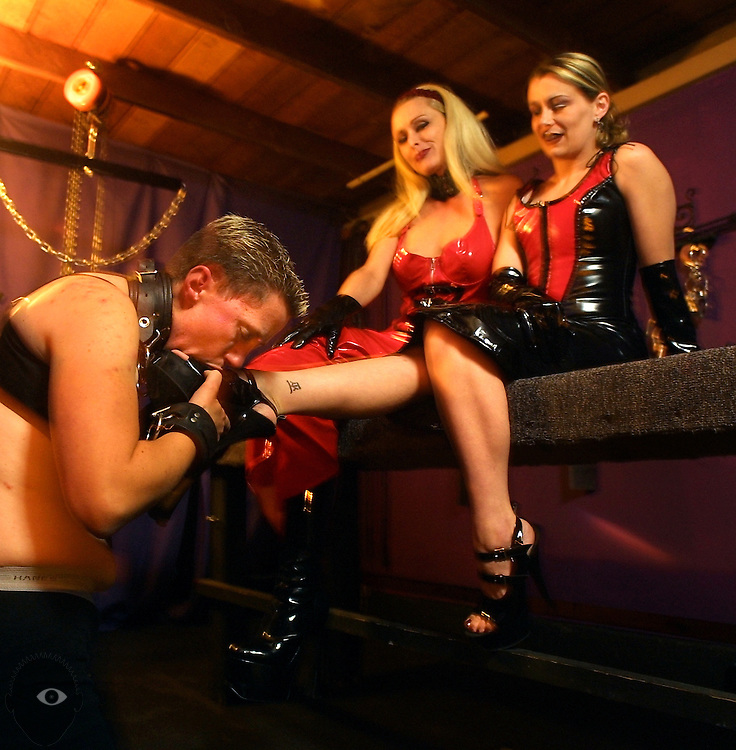May 18, 2003 - (LtoR) Submissive Trystan Askelson licks the shoes of Domina Goddess Severina Stern and her apprentice Soren Stern in her SE Portland, Oregon, room she calls the dungeon. Many seek out their services which can feature time on the rack, stock or being locked in a cage. This city has one of the most numerous sex-related businesses per capita  in the United States.