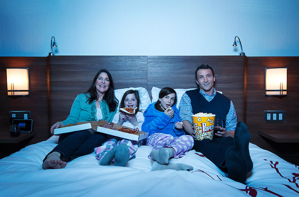 Advertising photography for Hotel Elan.<br /> Family sharing pizza and popcorn on bed while watching TV in a hotel.<br /> Hair &amp; Make-up Stylist: Shannon Payne<br /> Art Director: Judith Aldama<br /> Photography: Brett Gilmour