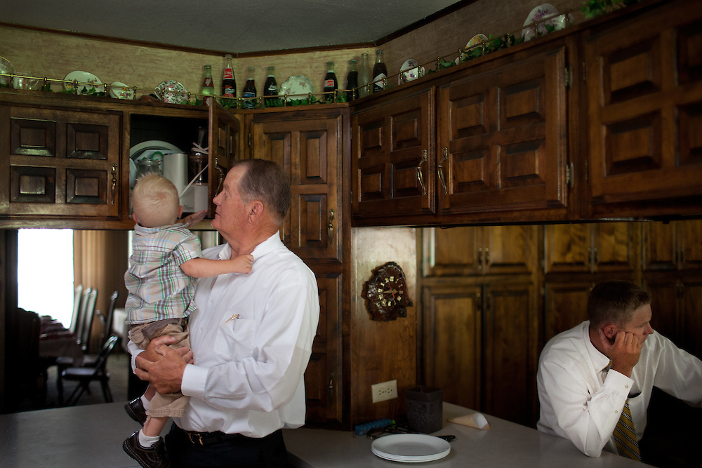 From left, Meredith Romney, holding his grandson Tyton, 1, and his son at right, Derrick, 32, hang out in the kitchen in Colonia Juarez, Mexico in July 2011. United States Presidential candidate Mitt Romney's family migrated to Mexico over 100 years ago after being granted asylum from Mexican President Porfirio Diaz after they had been pursued by the U.S. authorities for polygamy. ..(Romney is currently running for the Republican nomination.)