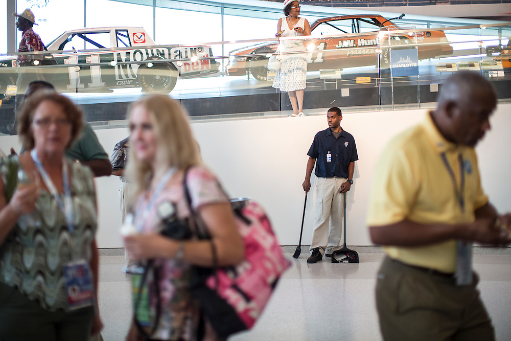 Guests mingle as a custodian keeps an eye out for trash at a welcome event for Democratic National Convention delegates from North Carolina, South Carolina, Virginia, Georgia and Tennessee at the NASCAR Hall of Fame on Sunday, September 2, 2012 in Charlotte, NC.