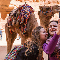 Jordan, Petra, Tourists take selfie snapshots beside camel in front of The Al Khazneh or The Treasury at Petra amid ancient ruins