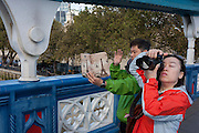 Tourists stop to take photos by one of Tower Bridge's giant Victorian-designed suspension chains. The bridge is undergoing repairs, closed to traffic and disrupting this major Thames crossing and surrounding roads for the next three months.