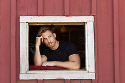 good looking man in deep thought looking out a barn window