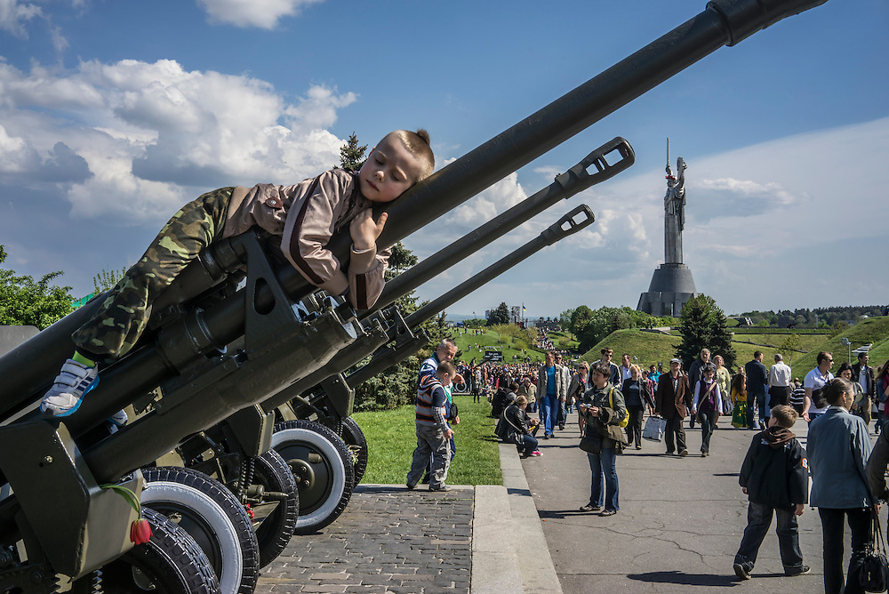 A child poses for a picture by his mother during Victory Day commemorations on Saturday, May 9, 2015 in Kyiv, Ukraine.